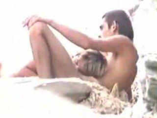 Sex am Strand, während der Mann Uhren