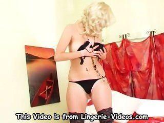 vollbusige blonde Cutie ihre Muschi in glänzenden schwarzen Strümpfen fingern
