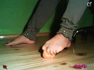 Mädchen Zerkleinern eines Mandarine mit ihren Füßen