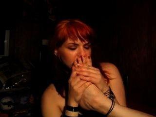 frechen Rotschopf schnüffelt ihre eigene stinkende Füße