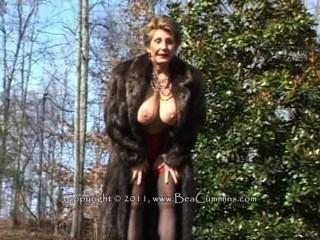 Dame in einem Pelzmantel masturbiert im Freien.