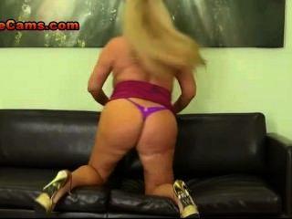 vollbusige Blondine spielt mit ihren Titten