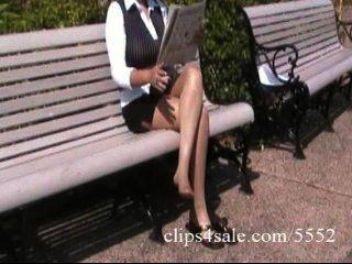 sexy drall latina Sekretärin zeigt ihre Beine in Strumpfhosen in einem Park aus